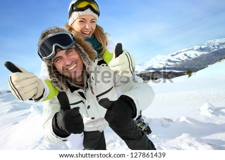 Cheerful snowboarder holding girlfriend on his back - stock photo