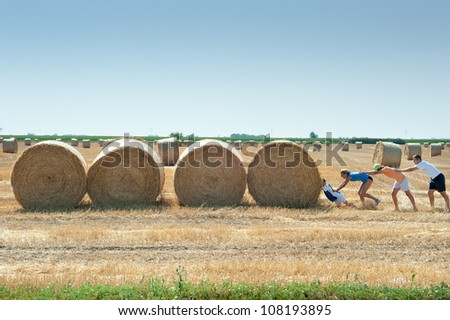 cheerful society are pushing straw bale - stock photo
