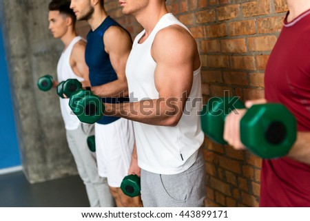Cheerful sportsmen exercising with weights - stock photo