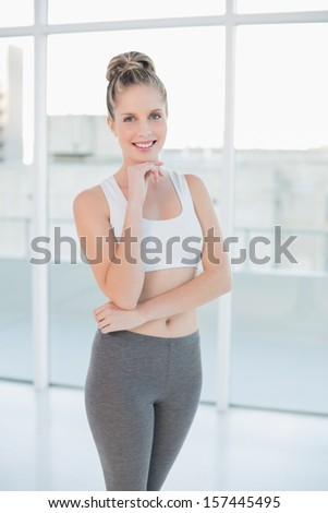Cheerful sporty blonde posing in bright room