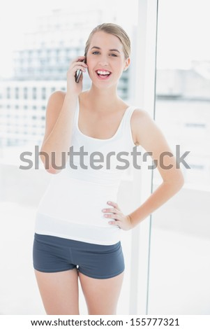 Cheerful sporty woman in bright sports hall on the phone - stock photo