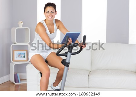 Cheerful sporty woman training on an exercise bike while holding a tablet smiling at camera - stock photo