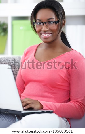 Cheerful student girl in living room with laptop - stock photo