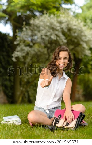Cheerful student girl sitting on grass shows thumb up summer - stock photo
