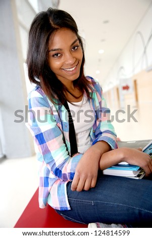 Cheerful student girl sitting on school bench - stock photo