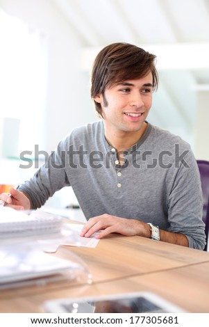 Cheerful student in class writing on document