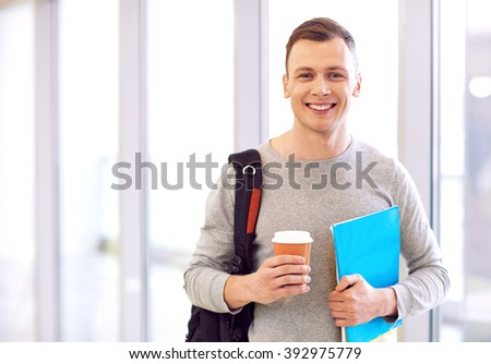 Cheerful student standing near window - stock photo