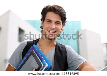 Cheerful student standing outside college building - stock photo