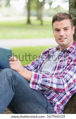 Cheerful student using his tablet pc outside leaning on tree on college campus - stock photo