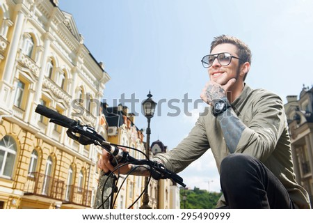 Cheerful styled man is sitting on the bicycle in the city. He is dreamingly looking aside and smiling - stock photo