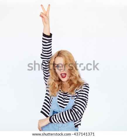 Cheerful stylish woman showing peace sign with fingers over white background. Young hipster blonde girl with clean face and red lips holding hand with 2 fingers gesture above head. - stock photo