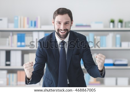 Cheerful successful businessman smiling in his office with raised fists, winning and enthusiasm concept