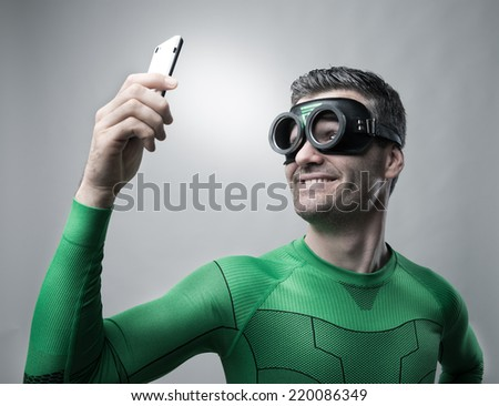 Cheerful superhero smiling and taking a selfie with a smartphone. - stock photo