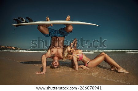 Cheerful surfing couple posing on the beach - stock photo