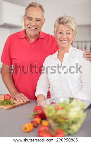 Cheerful Sweet Middle Aged Couple Standing at the Kitchen Table with Fresh Vegetables, Smiling at the Camera