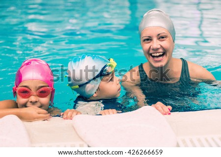 Cheerful swimming instructor having fun with children during swimming lesson. Toned image