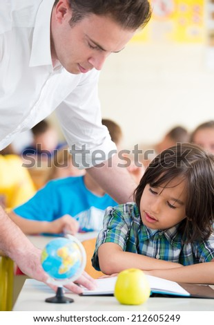 Cheerful teacher with kids learning in school classroom - stock photo