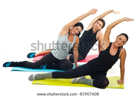 Cheerful team of three people doing fitness on colorful mats against white background - stock photo