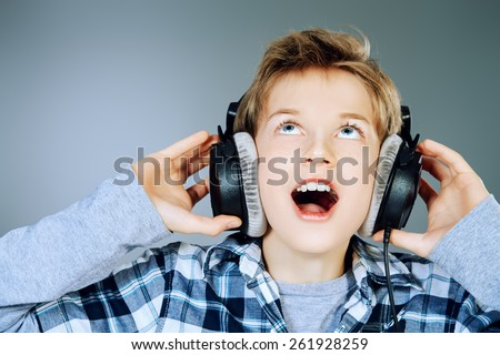 Cheerful teen boy listening to music in headphones and singing a song. Studio shot.  - stock photo