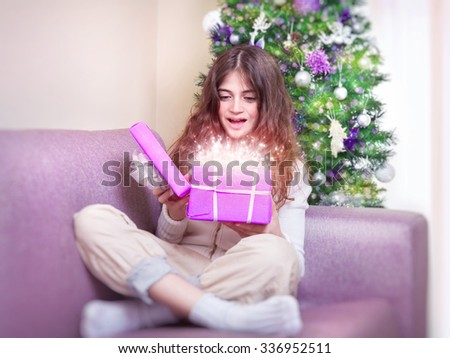 Cheerful teen girl opening gift box with magic glowing present, sitting on the couch near Christmas tree, happy winter holidays - stock photo