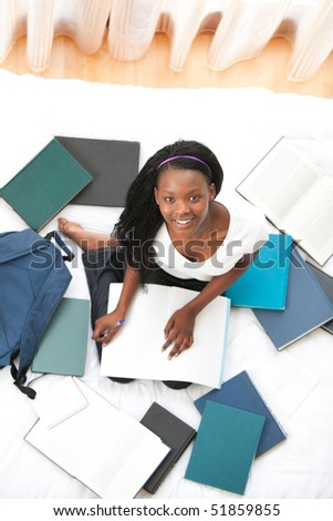 Cheerful teen girl studying sitting on her bed at home - stock photo