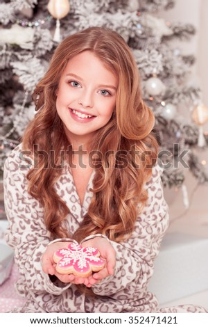 Cheerful teen girl 12-15 year old holding gingerbread in room. Christmas tree. Happy New year. - stock photo