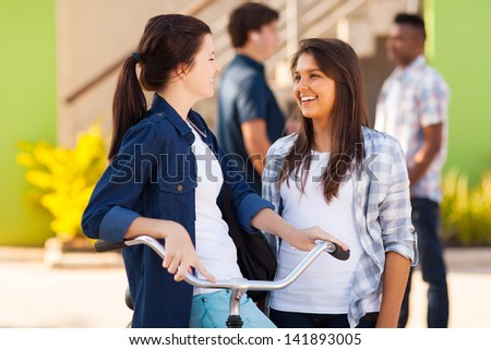 cheerful teenage friends girls talking outdoors - stock photo