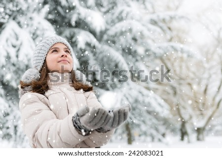 Cheerful, teenage girl looking in the sky, catching a snowflakes.Copy space - stock photo