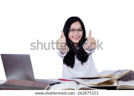 Cheerful teenage girl showing thumbs up at the camera while studying with laptop and books - stock photo