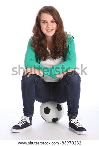 Cheerful teenage girl soccer player sitting on a football relaxing wearing green hoodie and blue jeans.