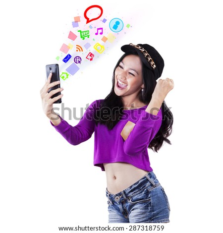 Cheerful teenage girl with trendy style using social media on her smartphone, shot in the studio - stock photo