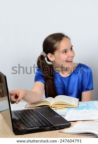 Cheerful teenage schoolgirl behind a desk trained with interest on the computer - stock photo