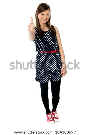 Cheerful teenager gesturing thumbs up isolated on white - stock photo