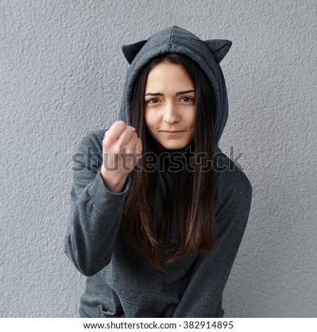 cheerful teenager girl threatens fist - stock photo