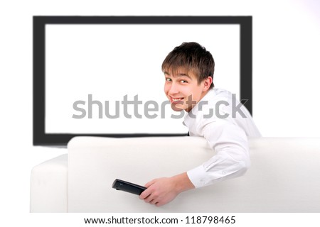 Cheerful Teenager sitting on the Sofa and watching Tv-set - stock photo