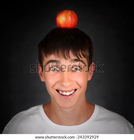 Cheerful Teenager with an Apple on the Head - stock photo