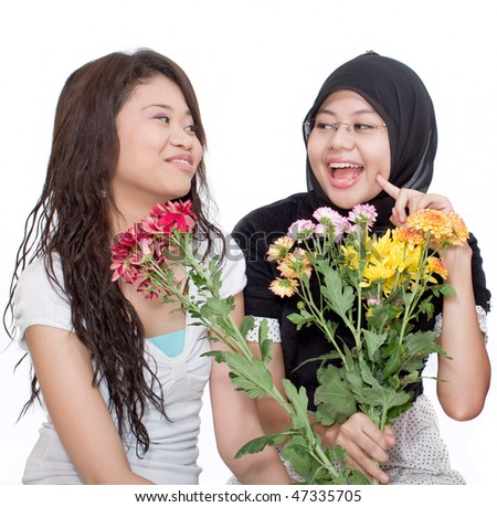 Cheerful teenagers hold flowers on isolated background