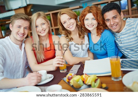 Cheerful teenagers spending free time in cafe together