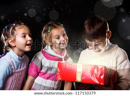 Cheerful teenagers with festive decoration on heads holding presents - stock photo