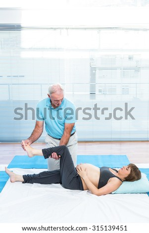 Cheerful therapist kneading to pregnant woman lying on mattress in clinic - stock photo