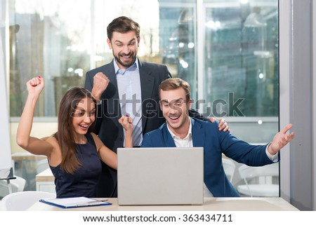 Cheerful three colleagues finished conference with success. The man and woman are sitting at table and gesturing happily. The young businessman is standing and looking at laptop with smile - stock photo