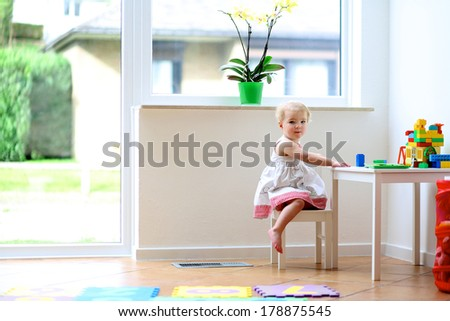 Cheerful toddler girl building house from plastic blocks sitting on a white table next to a big window at home or kindergarten - stock photo