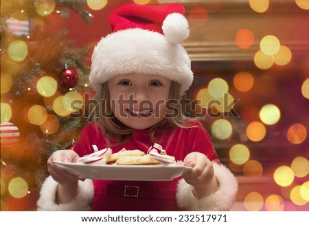 Cheerful toddler girl in hat holding plate with cookies and candy for santa claus - stock photo