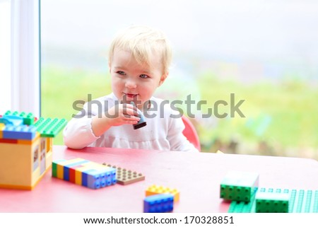 Cheerful toddler girl playing with plastic blocks sitting next to a big window  - stock photo