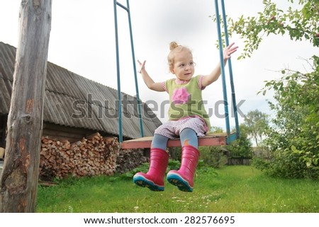 Cheerful toddler girl wearing red kids gumboots is riding on handmade rustic swing - stock photo