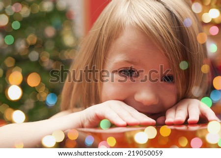 Cheerful toddler girl with Christmas lights  - stock photo