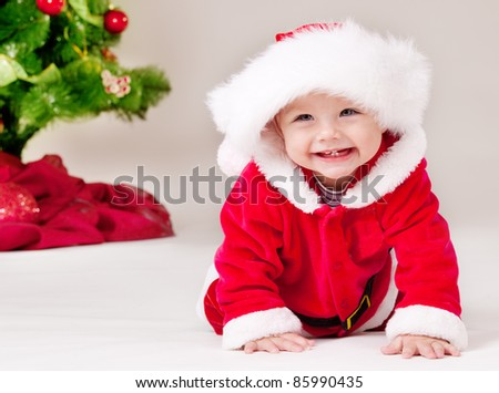 Cheerful toddler in Santa costume crawling - stock photo