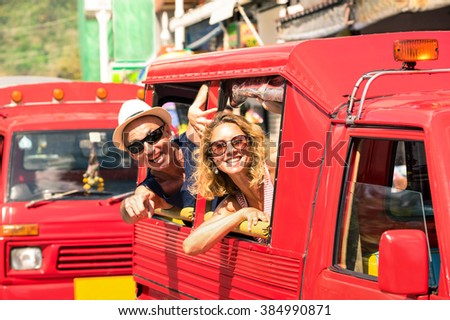 Cheerful tourist couple in tuk tuk thai taxi with pointing finger - Smiling friends having fun on road trip in Phuket island - Joyful people travel around the world - Concept of happiness on holiday - stock photo