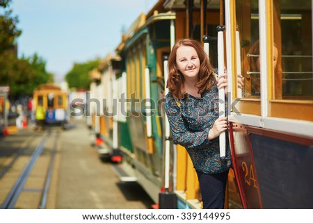 Cheerful tourist taking a ride in famous cable car in San Francisco, California, USA - stock photo