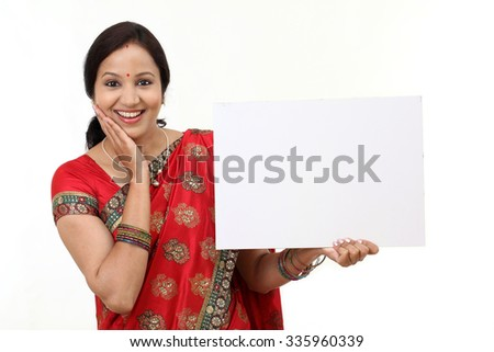 Cheerful traditional Indian woman holding a blank billboard - stock photo